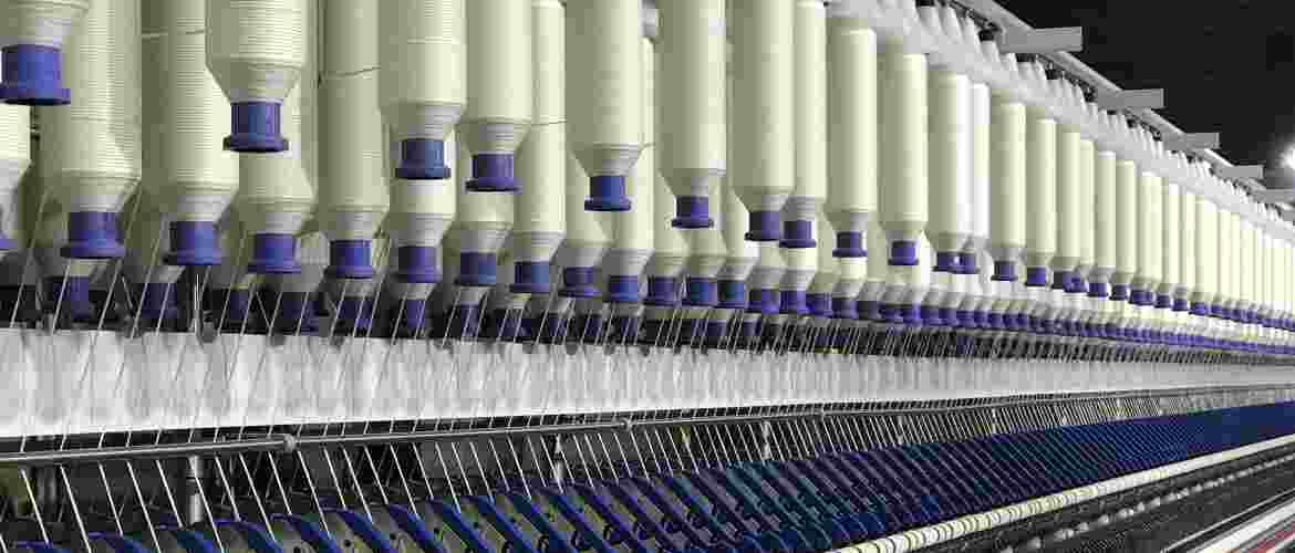 The spinning machines stake the roving, thin it and twist it, creating yarn. The roving is pulled off a bobbin and fed through rollers, which are feeding at several different speeds. This thins the roving at a consistent rate.